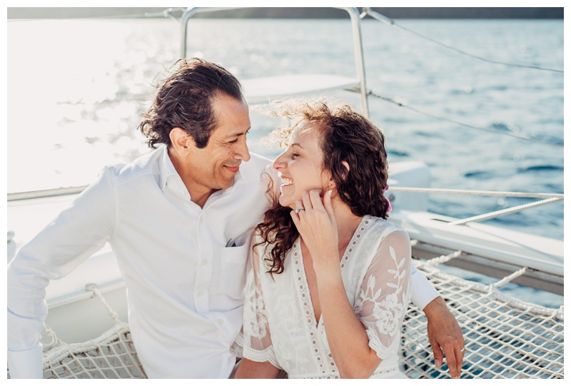 Bride and groom laughing on a sailboat during their magical sailboat elopement in Costa Rica. Photographed by Kristen M. Brown, Samba to the Sea Photography.