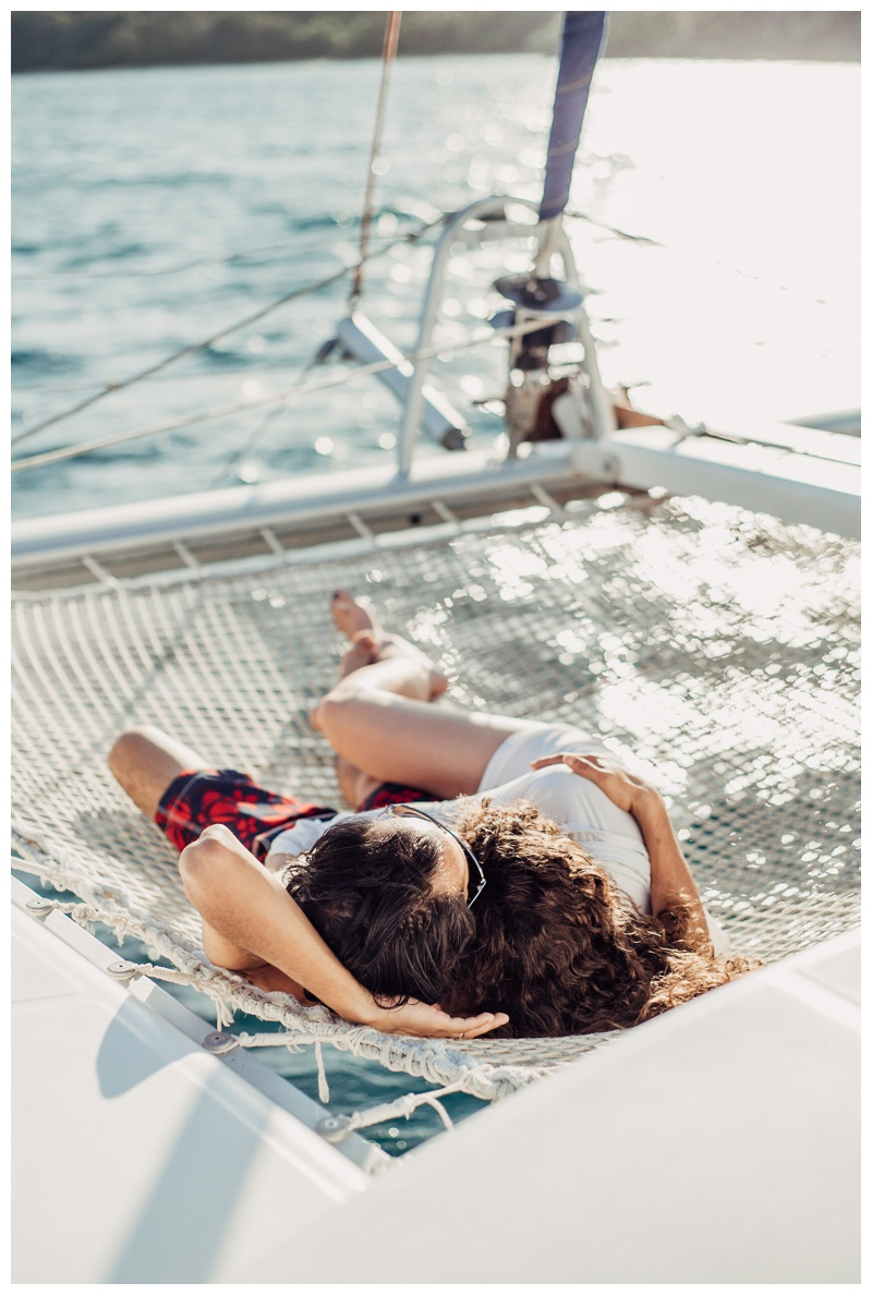Bride and groom relaxing on the boat during their magical sailboat elopement in Costa Rica. Photographed by Kristen M. Brown, Samba to the Sea Photography.