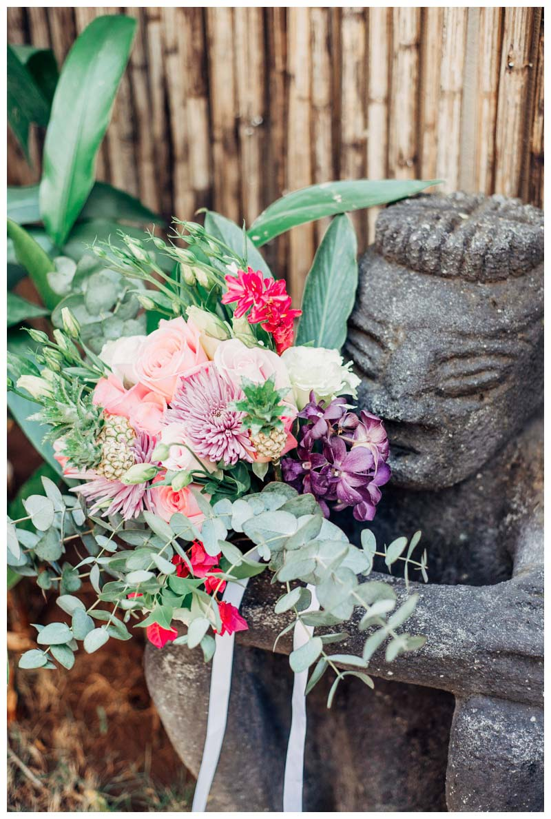 Monkey sculpture holding tropical bouquet. Boho elopement in Tamarindo Costa Rica. Photographed by Kristen M. Brown, Samba to the Sea Photography.
