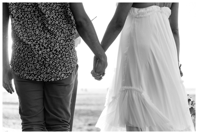 Bride and groom holding hands on the beach in Tamarindo Costa Rica. Photographed by Kristen M. Brown, Samba to the Sea Photography.