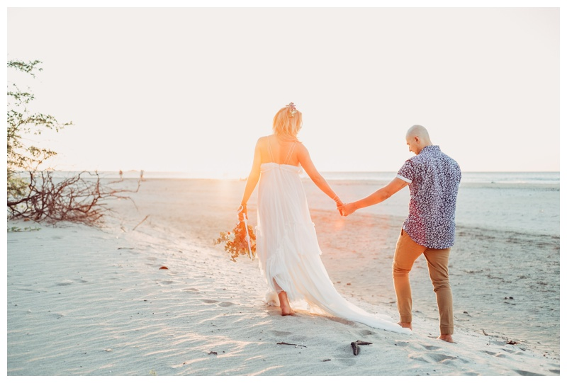 Bride and groom walking on the beach in Tamarindo Costa Rica. Photographed by Kristen M. Brown, Samba to the Sea Photography.