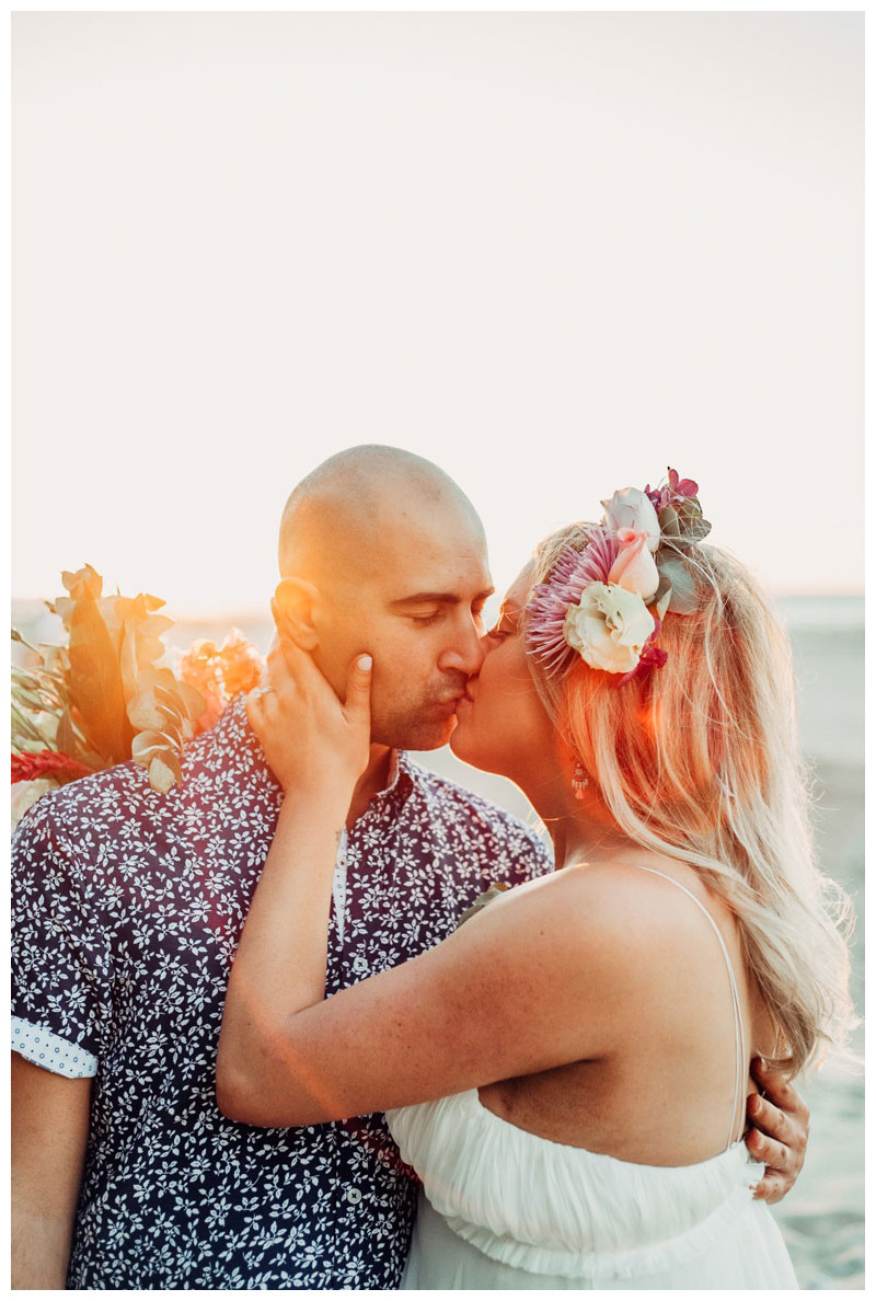 Bride and groom kissing on the beach in Tamarindo Costa Rica. Photographed by Kristen M. Brown, Samba to the Sea Photography.