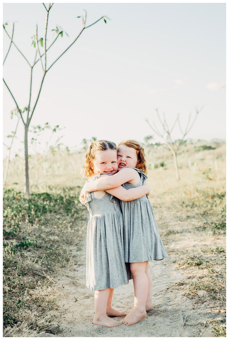 Sisters hugging on the beach in Nosara Costa Rica. Photographed by Kristen M. Brown, Samba to the Sea Photography.