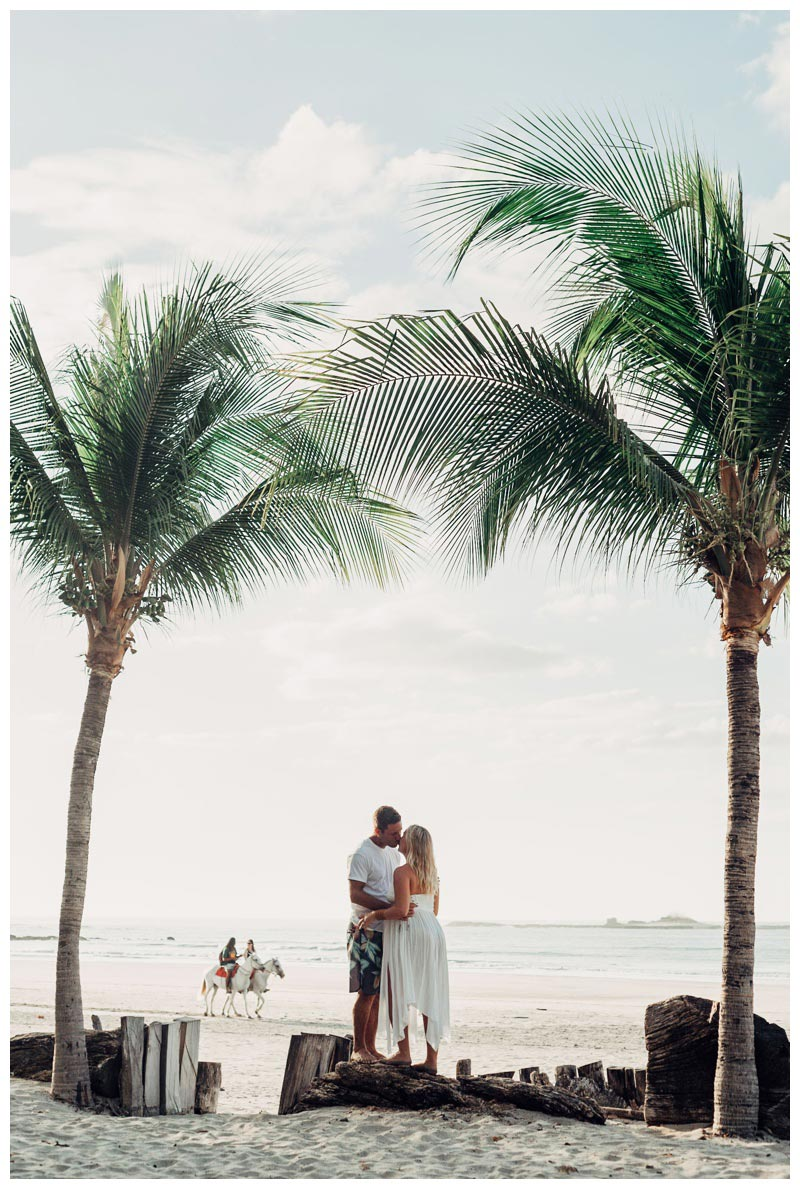 Couple kissing under palm trees on the beach during golden hour in Tamarindo Costa Rica. Photographed by Kristen M. Brown, Samba to the Sea Photography.