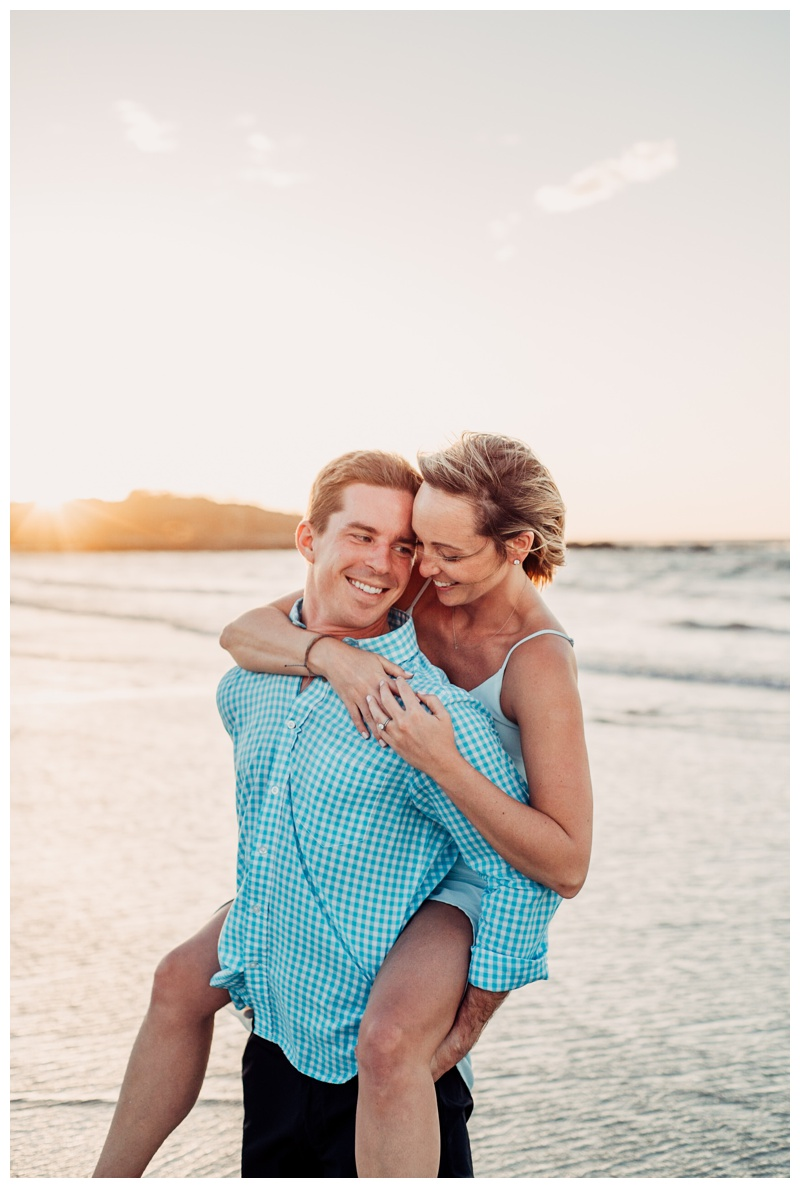 Husband giving his wife a piggy back ride on the beach in Tamarindo Costa Rica. Photographed by Kristen M. Brown, Samba to the Sea Photography.