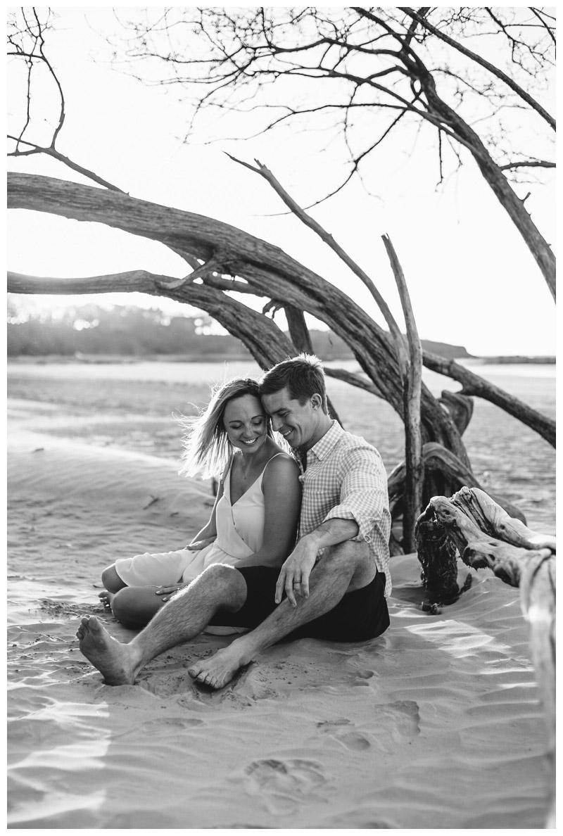 Couple sitting next to a beautiful piece of driftwood on the beach in Tamarindo Costa Rica. Photographed by Kristen M. Brown, Samba to the Sea Photography.