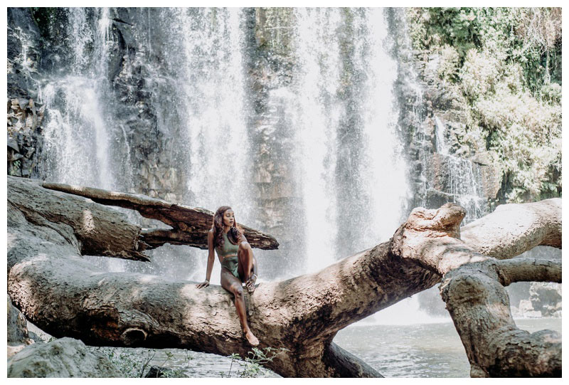 Woman sitting on a gorgeous tree branch at Llanos de Cortes waterfall in Costa Rica. One piece bathing suit BFYNE. Photographed by Kristen M. Brown, Samba to the Sea Photography.