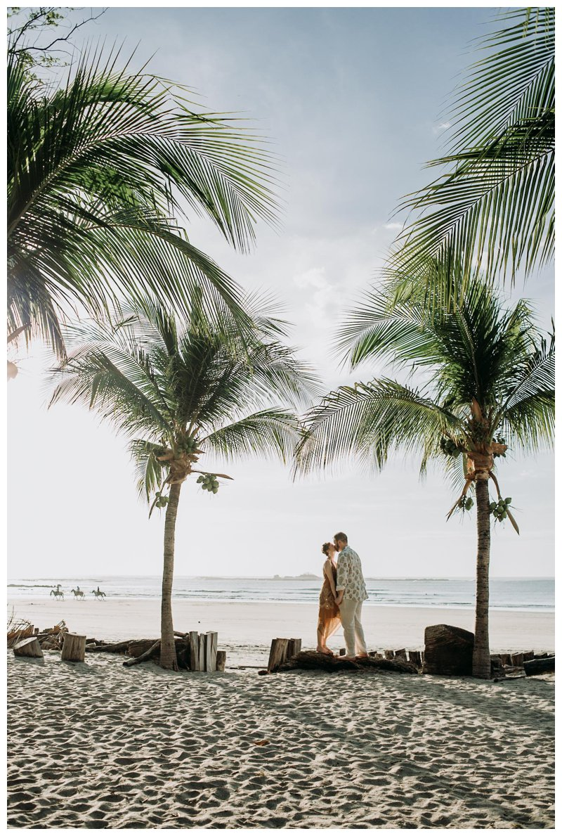 Couple kissing under palm tress on the beach in Tamarindo Costa Rica. Photographed by Kristen M. Brown, Samba to the Sea Photography.