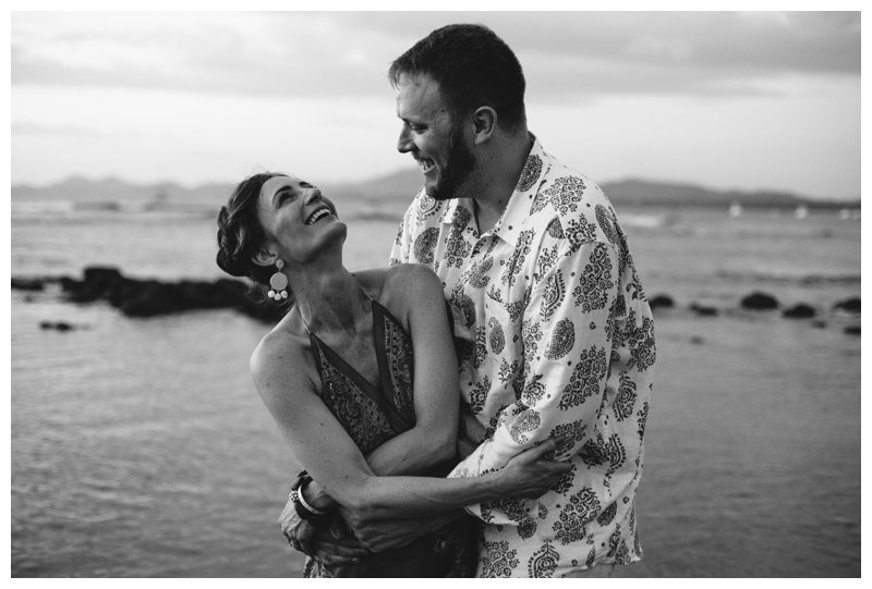 Black and white photo of couple laughing on the beach in Tamarindo Costa Rica. Photographed by Kristen M. Brown, Samba to the Sea Photography.