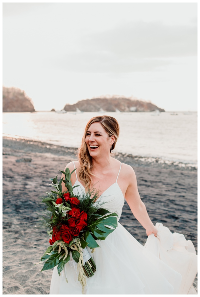 Bride laughing on the beach after wedding in Playa Ocotal Costa Rica. Photographed by Kristen M. Brown, Samba to the Sea Photography.
