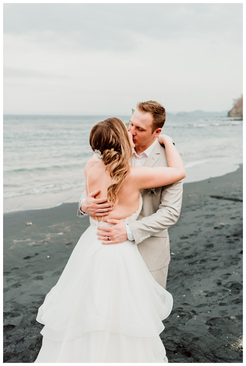 Bride and groom kissing on the beach after their wedding in Playa Ocotal Costa Rica. Photographed by Kristen M. Brown, Samba to the Sea Photography.