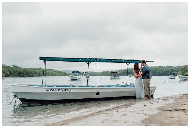 Bride and groom standing by a panga boat at the Tamarindo Estuary. Photographed by Kristen M. Brown, Samba to the Sea Photography.