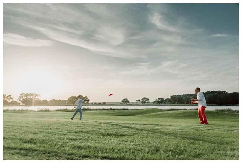 Dad playing frisbee with his son during family photos in Kiawah Island SC. Photographed by Kristen M. Brown, Samba to the Sea Photography.