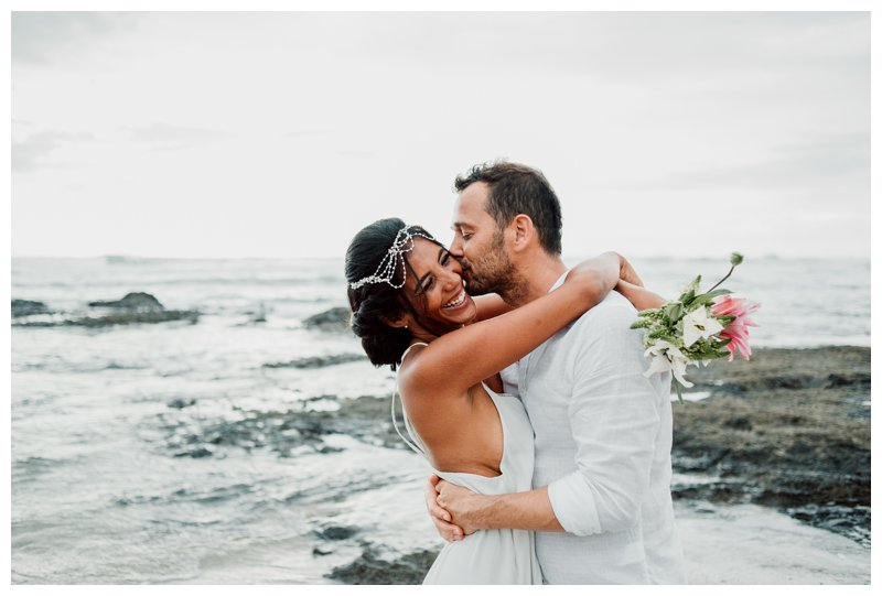 Groom kissing his bride during their boho beach elopement in Costa Rica. Photographed by Kristen M. Brown, Samba to the Sea Photography.