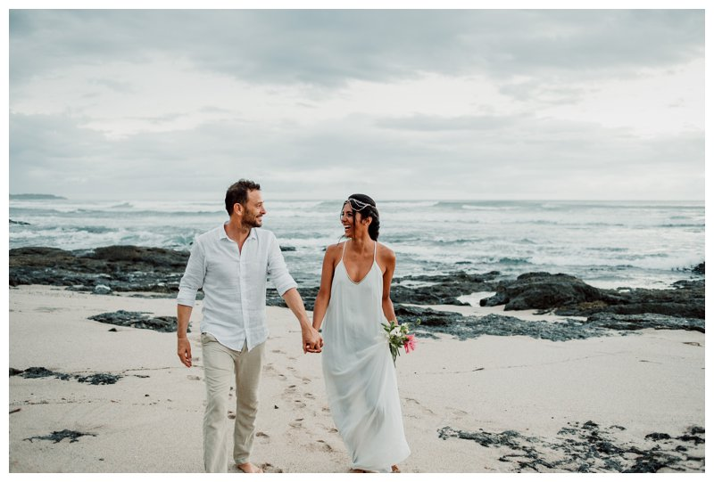 Bride and groom walking on the beach during their boho beach elopement in Costa Rica. Photographed by Kristen M. Brown, Samba to the Sea Photography.