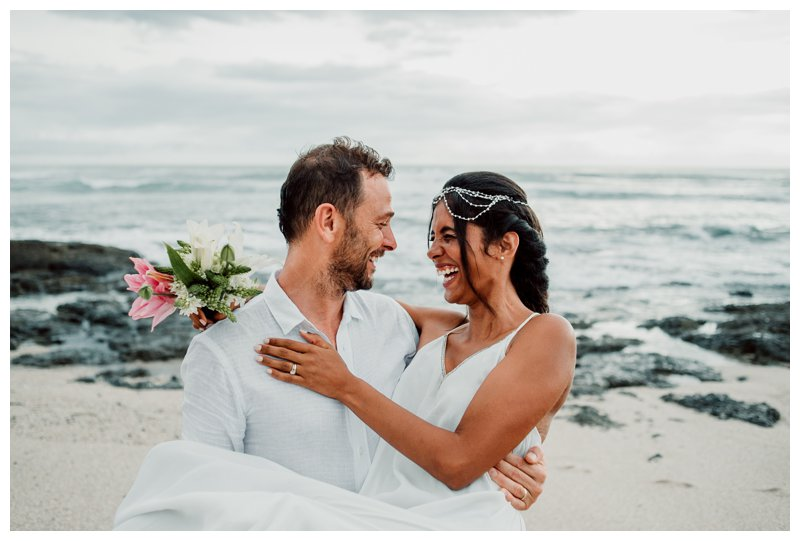 Groom carrying his bride on the beach during their boho beach elopement in Costa Rica. Photographed by Kristen M. Brown, Samba to the Sea Photography.