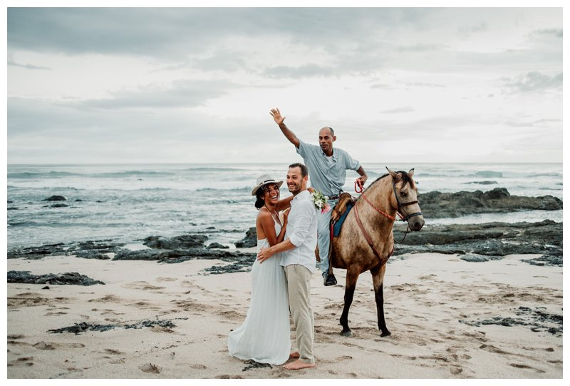 Caballero and his horse photobombing a boho beach elopement in Costa Rica. Photographed by Kristen M. Brown, Samba to the Sea Photography.