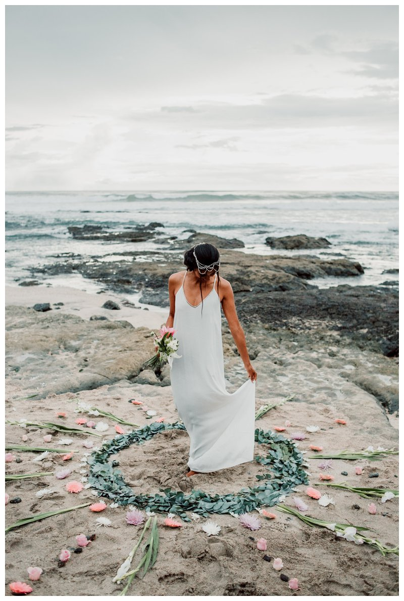 Bride and a flower mandala on the beach during their boho beach elopement in Costa Rica. Photographed by Kristen M. Brown, Samba to the Sea Photography.