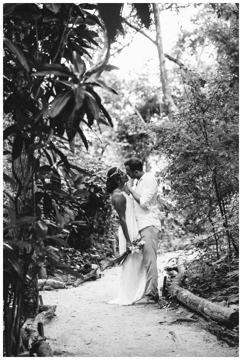 Bride and groom kissing in tropical gardens during their boho beach elopement in Costa Rica. Photographed by Kristen M. Brown, Samba to the Sea Photography.