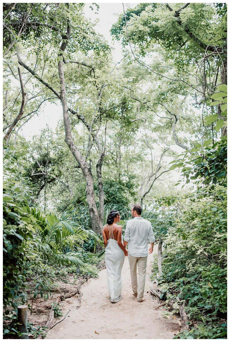 Bride and groom in tropical gardens during their boho beach elopement in Costa Rica. Photographed by Kristen M. Brown, Samba to the Sea Photography.