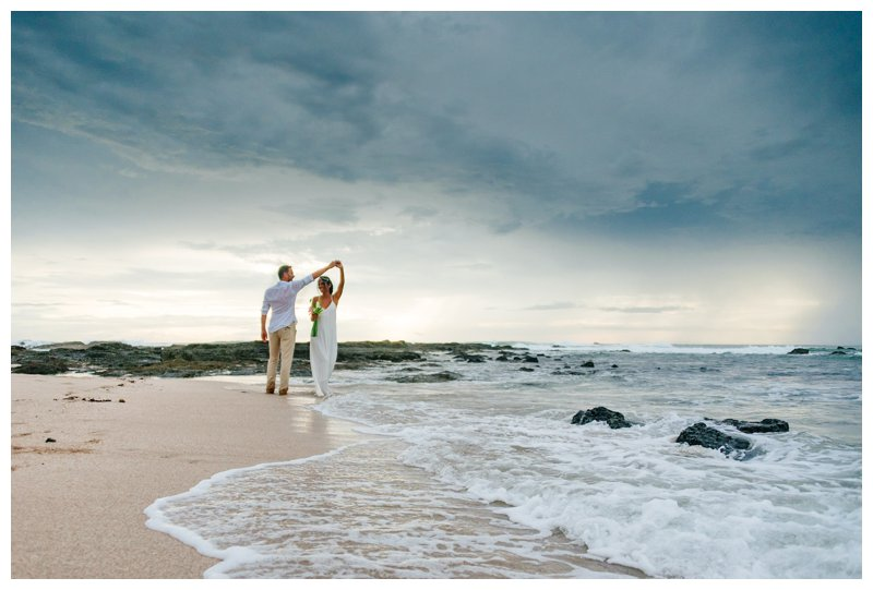 Groom spinning his bride during their boho beach elopement in Costa Rica. Photographed by Kristen M. Brown, Samba to the Sea Photography.