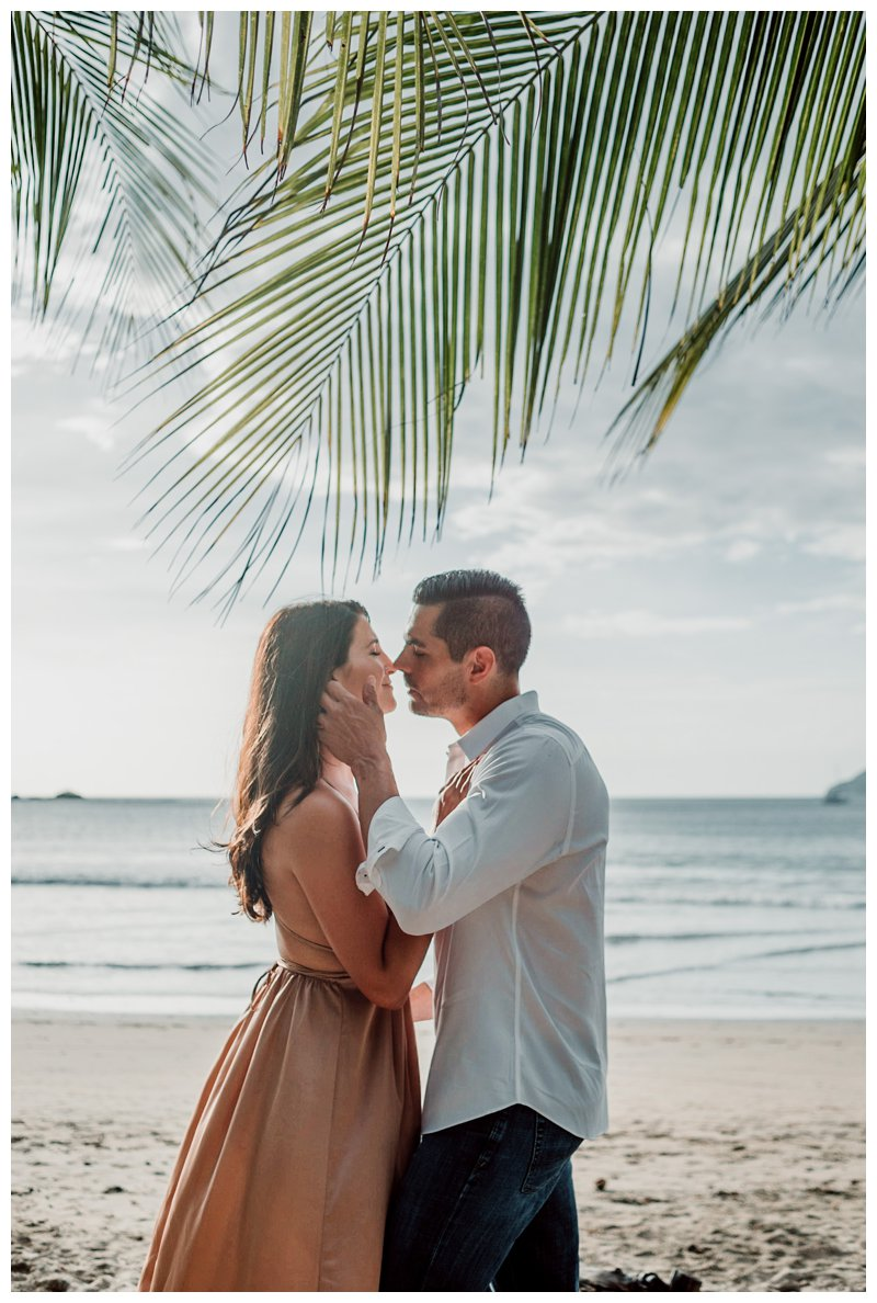 Couple kissing under palm trees during honeymoon photos in Tamarindo Costa Rica. Photographed by Kristen M. Brown, Samba to the Sea Photography.