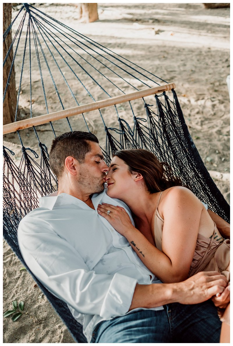 Couple kissing in a hammock under palm trees during honeymoon photos in Tamarindo Costa Rica. Photographed by Kristen M. Brown, Samba to the Sea Photography.