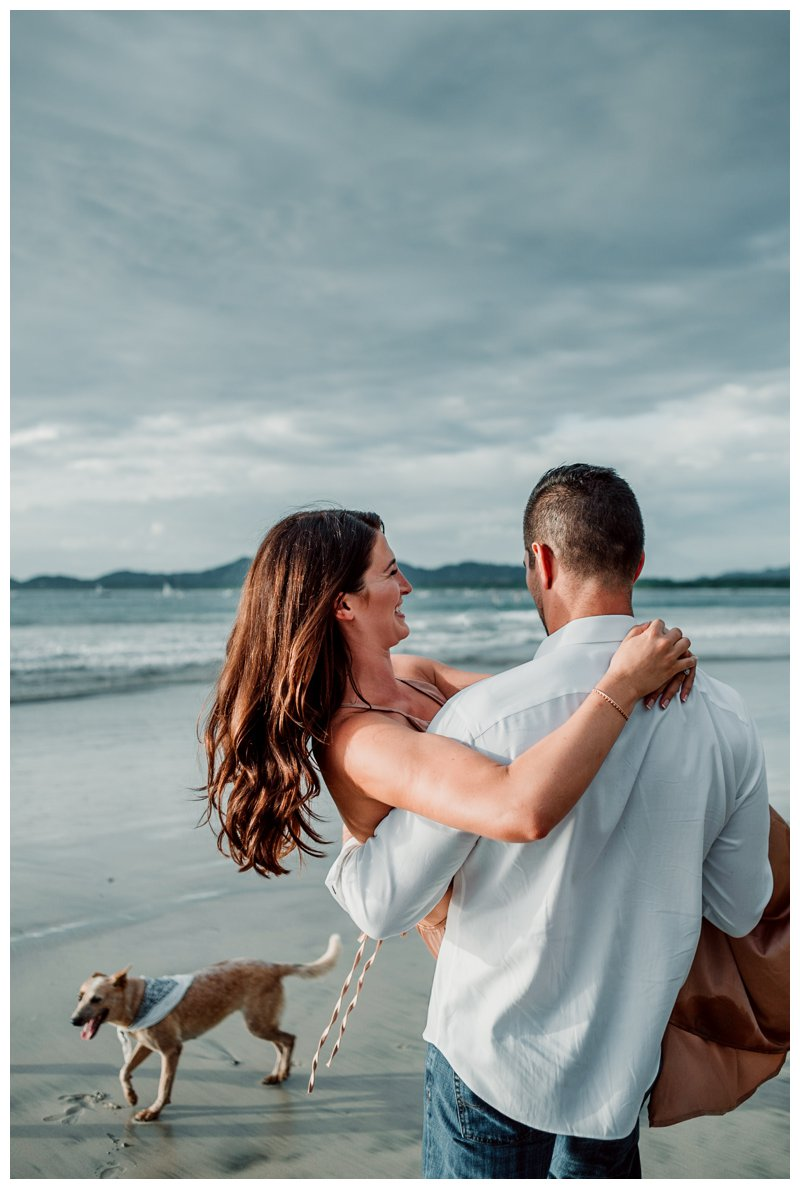 Husband carrying his wife on the beach during honeymoon photos in Tamarindo Costa Rica. Photographed by Kristen M. Brown, Samba to the Sea Photography.