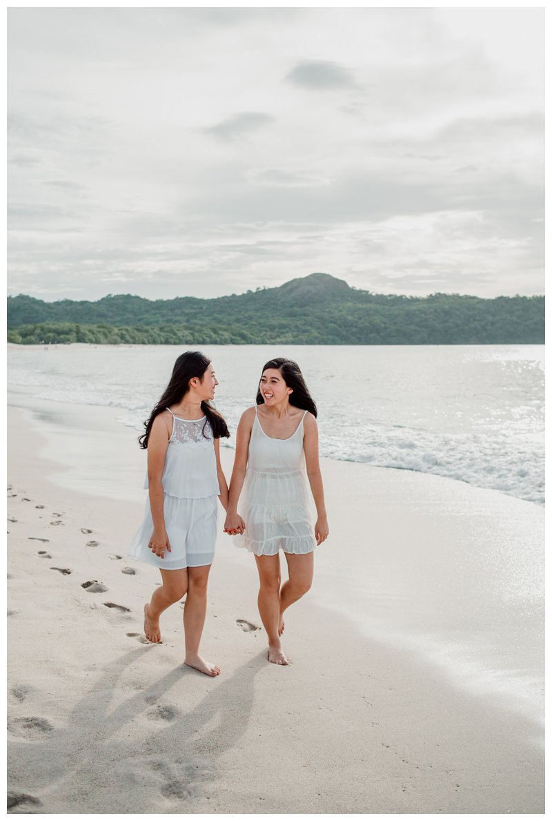 Sisters walking on the beach during family photos in Playa Conchal. Photographed by Kristen M. Brown, Samba to the Sea Photography.