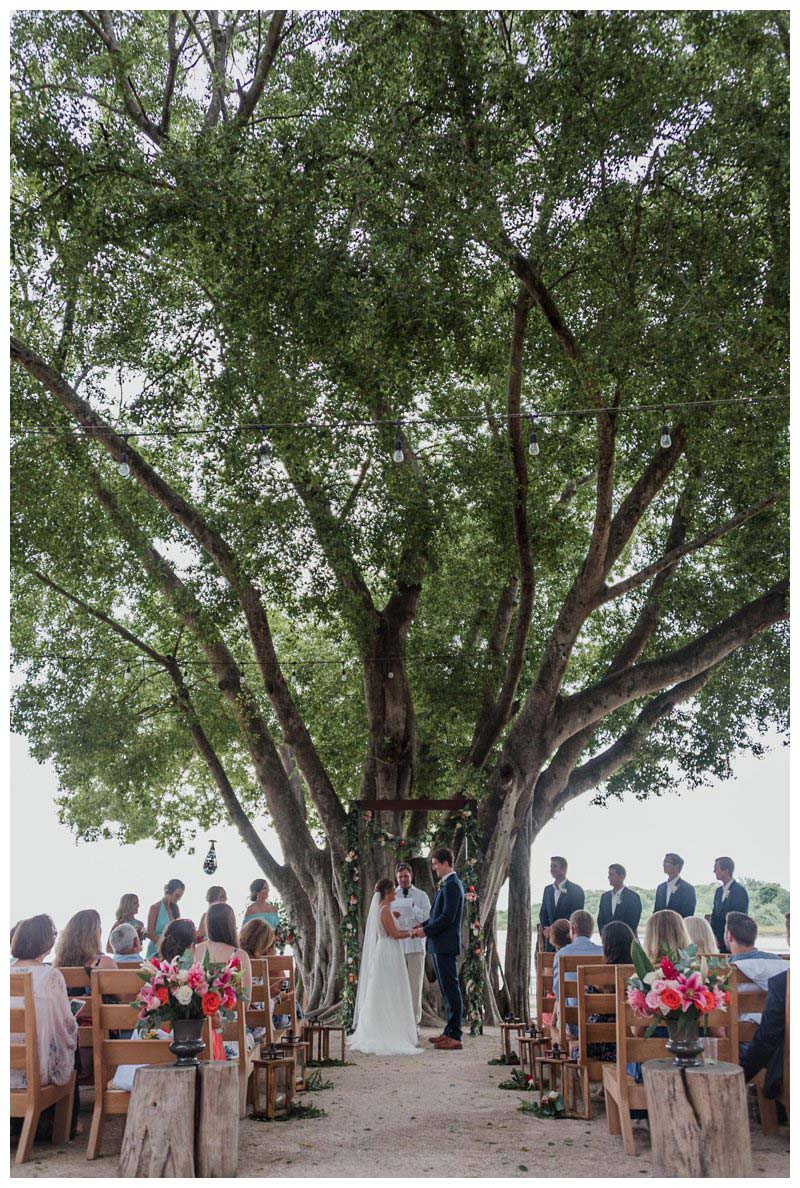 Bride and groom standing under a tree during their tropical wedding at Pangas Beach Club in Tamarindo Costa Rica. Photographed by Kristen M. Brown, Samba to the Sea Photography.