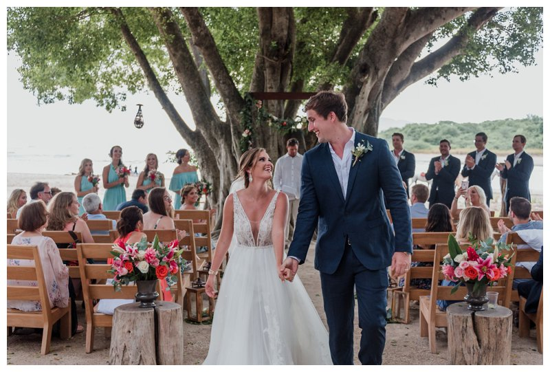 Bride and groom walking down the aisle after their ceremony of tropical wedding at Pangas Beach Club in Tamarindo Costa Rica. Photographed by Kristen M. Brown, Samba to the Sea Photography.