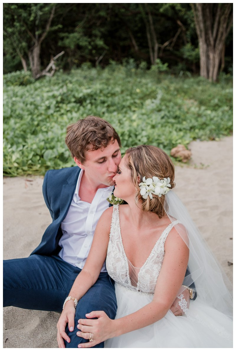 Groom kissing his bride on the beach after their ceremony of tropical wedding at Pangas Beach Club in Tamarindo Costa Rica. Photographed by Kristen M. Brown, Samba to the Sea Photography.