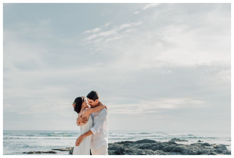 Bride and groom embracing on the beach after their beach elopement in Playa Langosta Costa Rica. Photographed by Kristen M. Brown, Samba to the Sea Photography.