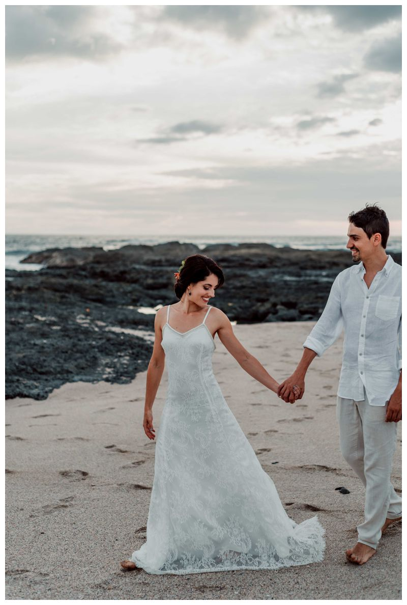 Bride leading her husband on the beach after their beach elopement in Playa Langosta Costa Rica. Photographed by Kristen M. Brown, Samba to the Sea Photography.