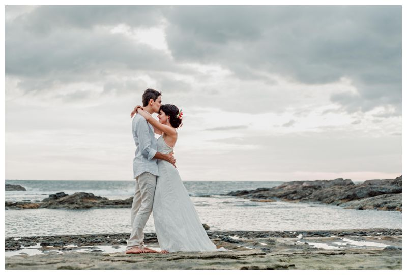 Groom kissing his bride on the forehead on the low tide rocks after their beach elopement in Playa Langosta Costa Rica. Photographed by Kristen M. Brown, Samba to the Sea Photography.
