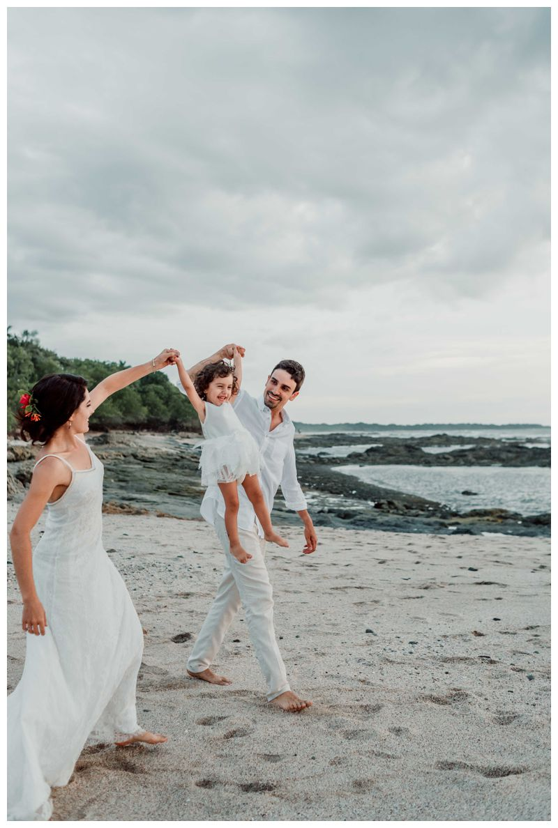 Bride and groom playing with their daughter on the beach after their beach elopement in Playa Langosta Costa Rica.Photographed by Kristen M. Brown, Samba to the Sea Photography.