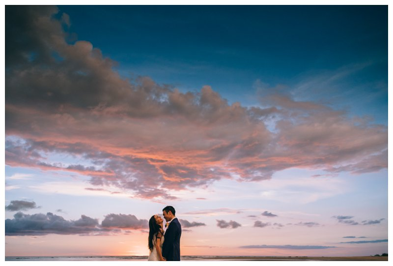 Bride and groom laughing during sunset on the beach at their beach wedding in Tamarindo Costa Rica at Pangas Beach Club. Photographed by Kristen M. Brown, Samba to the Sea Photography.