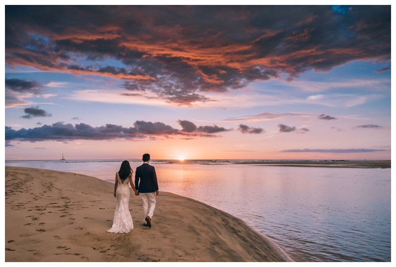 Bride and groom walking on the beach during sunset on the beach at their beach wedding in Tamarindo Costa Rica at Pangas Beach Club. Photographed by Kristen M. Brown, Samba to the Sea Photography.