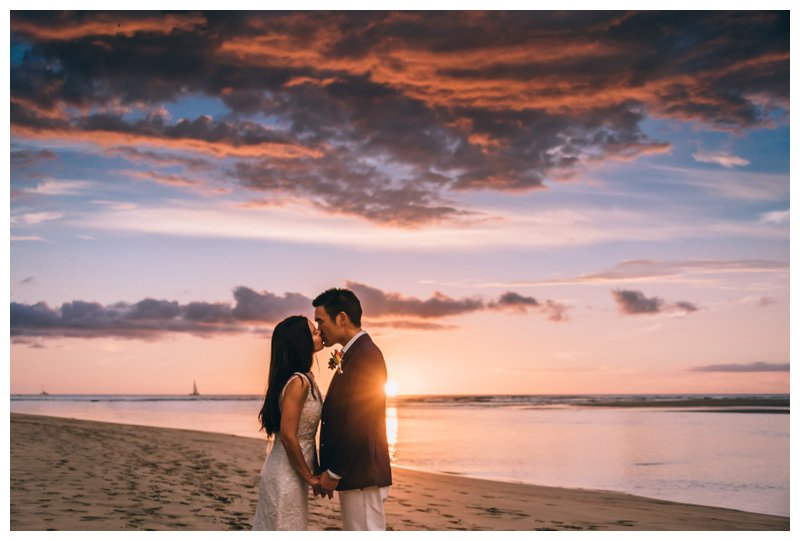 Bride and groom kissing during sunset on the beach at their beach wedding in Tamarindo Costa Rica at Pangas Beach Club. Photographed by Kristen M. Brown, Samba to the Sea Photography.