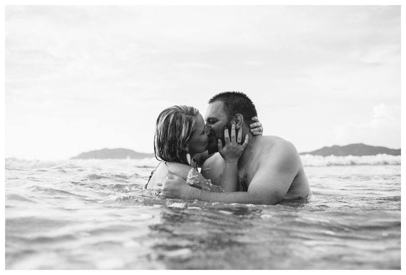 Husband and wife kissing in the ocean during lifestyle photos in Tamarindo Costa Rica. Photographed by Kristen M. Brown, Samba to the Sea Photography.