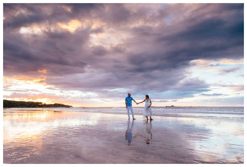 Couple holding hands on the beach in Tamarindo Costa Rica during sunset. Photographed by Kristen M. Brown, Samba to the Sea Photography.