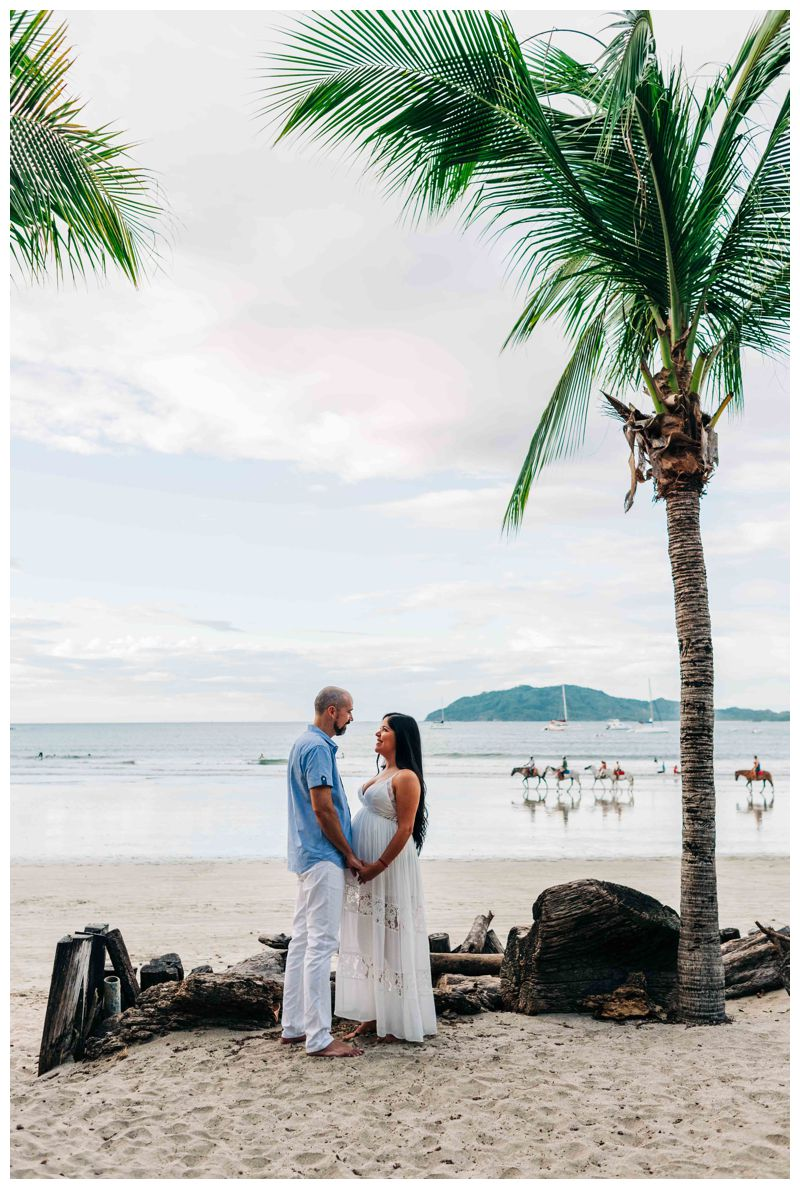 Couple standing under a palm tree on the beach during maternity photos in Costa Rica. Photographed by Kristen M. Brown, Samba to the Sea Photography.