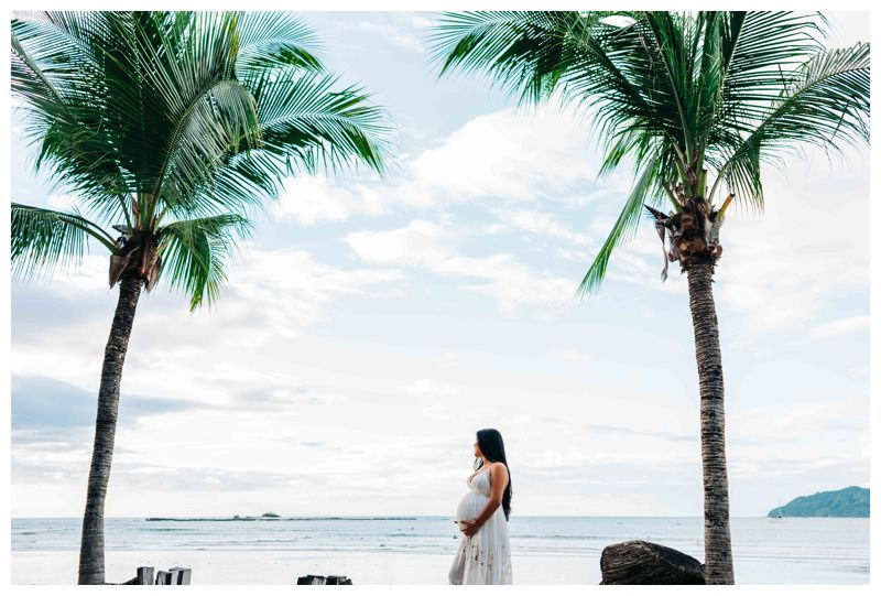 Pregnant woman standing under a palm tree on the beach during maternity photos in Costa Rica. Photographed by Kristen M. Brown, Samba to the Sea Photography.