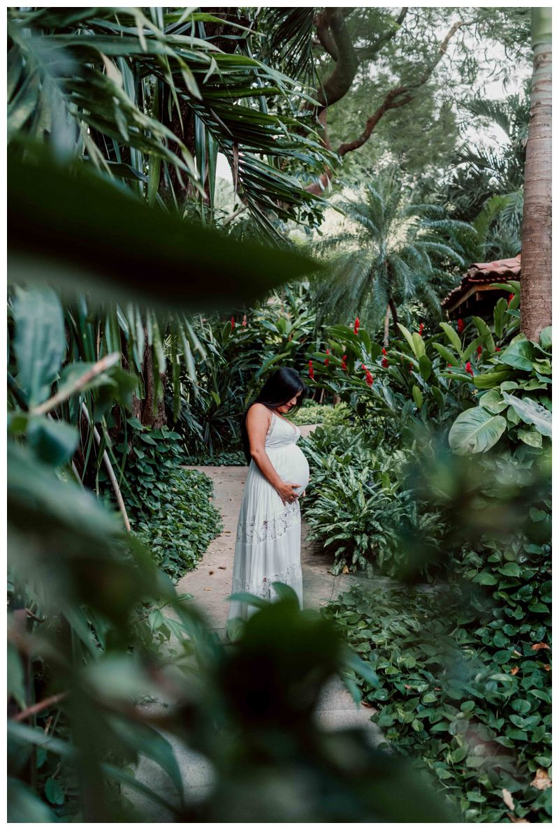 Pregnant woman standing in a tropical garden during maternity photos in Costa Rica. Photographed by Kristen M. Brown, Samba to the Sea Photography.