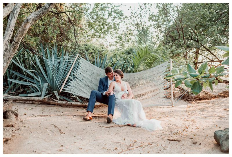 Bride and groom sitting in a hammock on the beach at Cala Luna Boutique Hotel. Beach wedding in Tamarindo Costa Rica at Langosta Beach Club photographed by Kristen M. Brown, Samba to the Sea Photography.