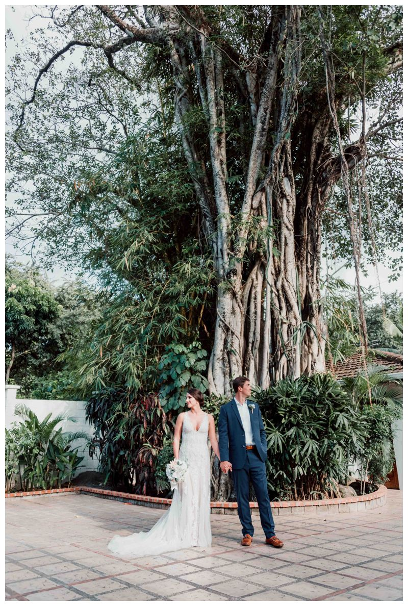 Bride and groom in front of a Banyan tree in Costa Rica. Beach wedding in Tamarindo Costa Rica at Langosta Beach Club photographed by Kristen M. Brown, Samba to the Sea Photography.