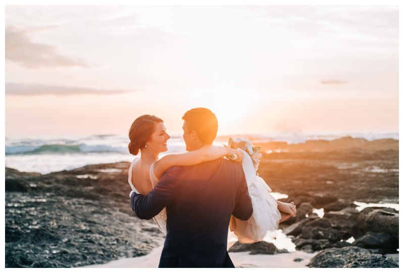 Groom carrying his bride on the beach during sunset in Costa Rica. Beach wedding in Tamarindo Costa Rica at Langosta Beach Club photographed by Kristen M. Brown, Samba to the Sea Photography.