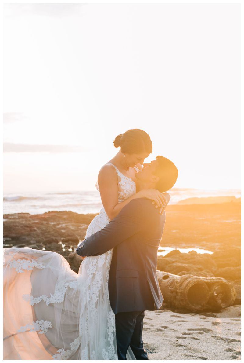 Groom holding his bride on the beach during sunset in Costa Rica. Beach wedding in Tamarindo Costa Rica at Langosta Beach Club photographed by Kristen M. Brown, Samba to the Sea Photography.