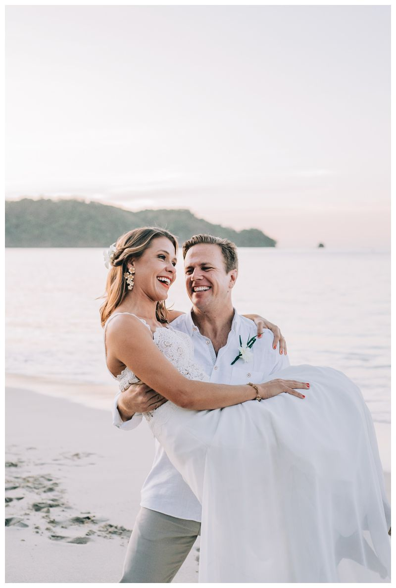 Groom carrying his bride on the beach. Wedding portraits on the beach in Costa Rica. Beach wedding in Playa Conchal Costa Rica photographed by Kristen M. Brown, Samba to the Sea Photography.