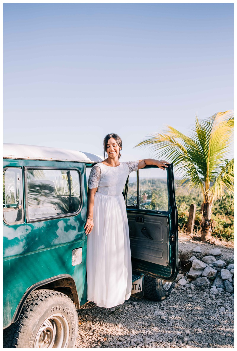 Bride and a Toyota Land Cruise J40 before her beach elopement in Samara Costa Rica. Photographed by Kristen M. Brown, Samba to the Sea Photography.